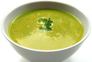 Grüne Bärlauchsuppe mit einem Petersilieblatt dekoriert in weißer Suppenschale